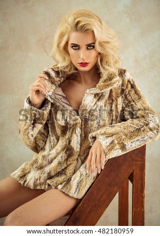Sexy blonde woman wear fur and posing