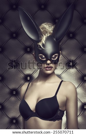 Sexy blonde woman with curly hair-style posing in sexy lingerie with  black bunny carnival mask. Gothic Easter