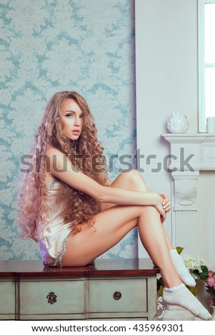 Sexy blonde woman with fashion make-up and curly hair in vintage bedroom. Skin and hair care concept - stock photo