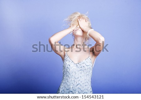 Sexy blonde woman with hands on her head - stock photo