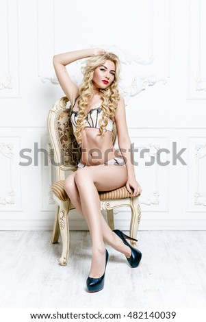 Sexy blonde woman with long curly hair in lingerie