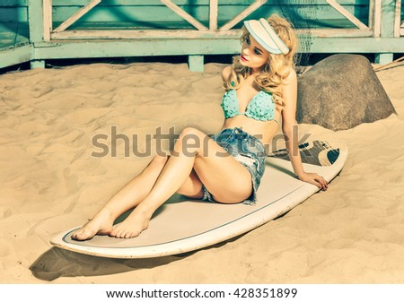 sexy blonde young woman in swimsuit and jeans shorts sitting on serfboard on sand beach - stock photo