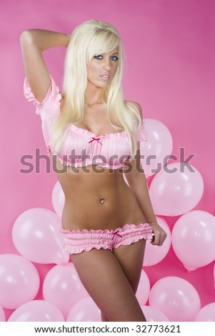 sexy blue eyed blond in pink bra and ruffled panties with balloons and pink background