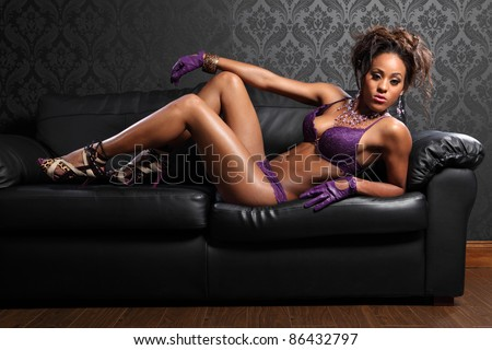 Sexy body of beautiful young african american glamour model woman wearing purple lace lingerie and leather gloves, lying on black leather sofa with killer stiletto heels. - stock photo