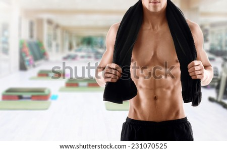Sexy body of muscular athletic man with towel on the shoulders in gym - stock photo