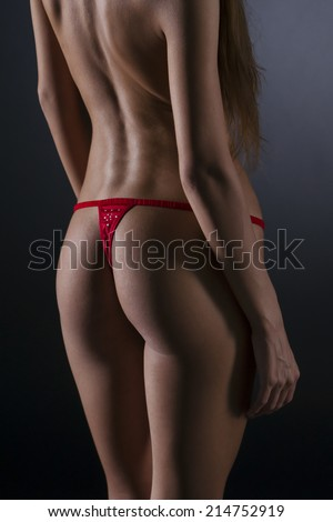 Sexy body on a gray background. Naked beautiful young woman.