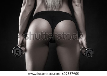 Sexy bodybuilder ass closeup, holding two 5kg dumbbells