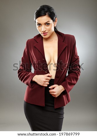 Sexy bra-less hispanic businesswoman with only her jacket, partly letting beautiful breasts to be seen - stock photo