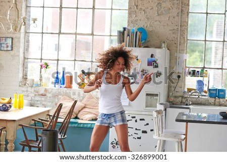 Sexy brazilian girl dancing at home wearing checked pajamas shorts throwing hair back - stock photo