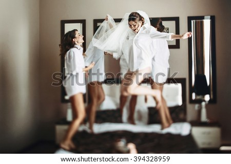 Sexy bride & bridesmaids jumping on bed before wedding - stock photo
