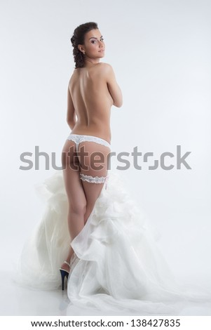 Sexy bride in lingerie posing back to camera - stock photo