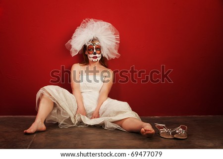 Sexy bride in makeup for All Souls Day sits on the ground - stock photo