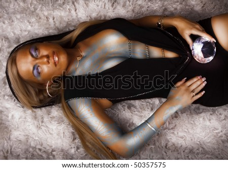 Sexy bronze woman lying with gem in hands - stock photo