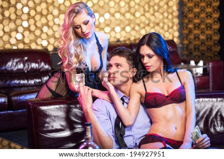 Sexy brunet striptease dancer dancing lap dance.  While man giving tips to beautiful blond striptease dancer   - stock photo