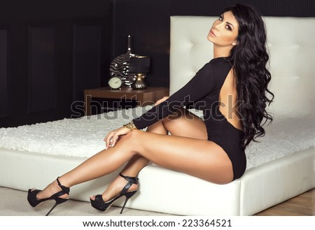 Sexy brunette beautiful woman posing in lingerie. Girl with perfect slim body in bedroom. Studio shot. - stock photo