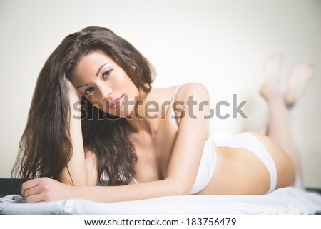 Sexy brunette caucasian woman laying on the bed