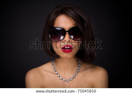 sexy brunette elegant woman expressed wearing neckles  and sunglasses