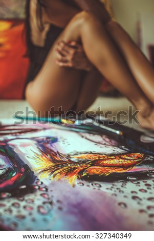 Sexy brunette female sitting on the floor with picture. - stock photo
