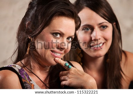Sexy brunette females looking over and smiling - stock photo