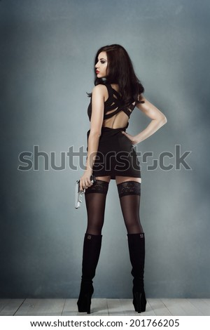 sexy brunette girl in a black dress boots holding a gun and looking back - stock photo