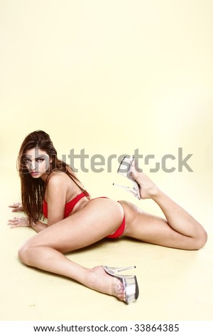 Sexy brunette Girl in red  lingerie on knees light play green background - stock photo