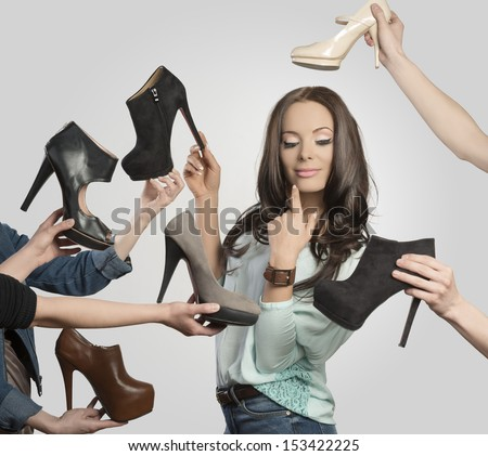 sexy brunette girl in shopping time posing surrounded by assortment of shoes. Looking shoes and smiling