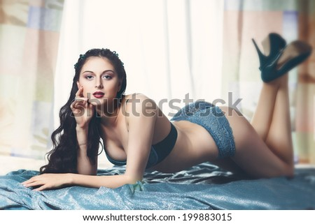sexy brunette girl lying on the floor in stockings and blue lingerie and blue shoes - stock photo