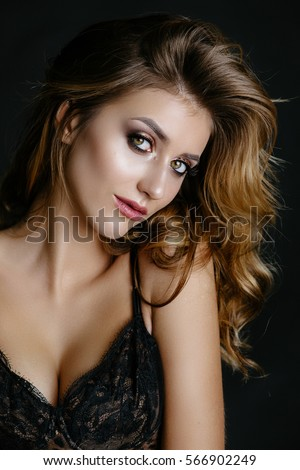 sexy brunette girl posing in leopard print bodysuit studio on a black background. Advertising Space