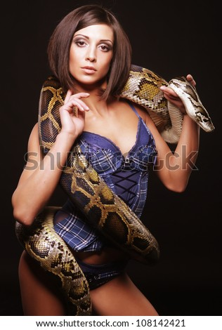 sexy brunette holding python over black background - stock photo