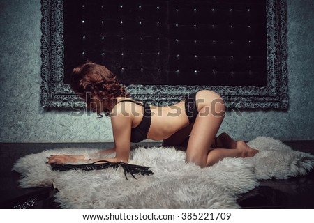 Sexy brunette in black lingerie of excited submissive  waiting for his sentenceon on the white carpet. Side view. Dark background. Bdsm. - stock photo