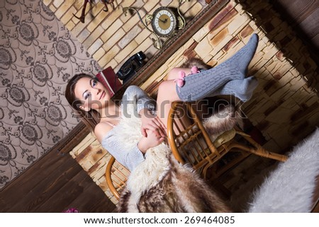 Sexy brunette in grey stockings sitting on the chair near a fireplace - stock photo