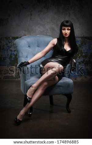 Sexy brunette in leather dress is sitting on the chair - stock photo