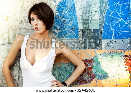 Sexy brunette lady in white shirt standing near a brick wall - stock photo