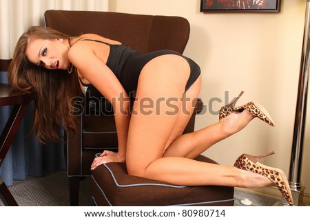 Sexy brunette lingerie model with long legs bending over - stock photo
