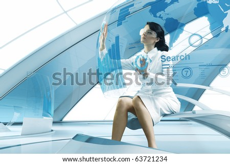 Sexy brunette operating transparent future touch interface. Sits in the air chair. Impressive specially designed for this series abstract bio interior. Interfaces collection. - stock photo