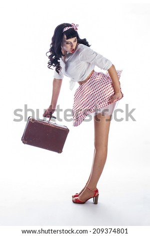 Sexy brunette pin up girl wearing pink skirt holding a little suitcase.  - stock photo