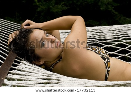 Sexy brunette posing in patterned bikini while laying outside on a sunny day - stock photo