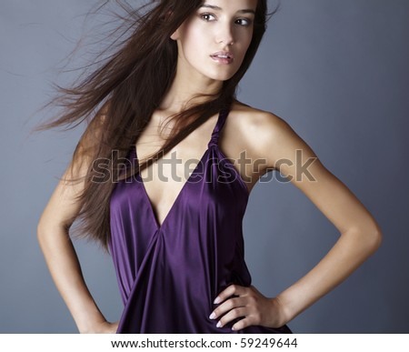 Sexy brunette posing in silk violet dress. - stock photo