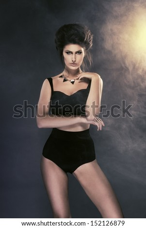 Sexy brunette posing on dark background with light and smoke