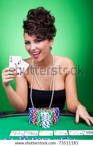 sexy brunette showing winning hand at poker table - four aces