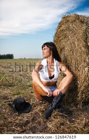 Sexy brunette sitting near a straw bale. - stock photo