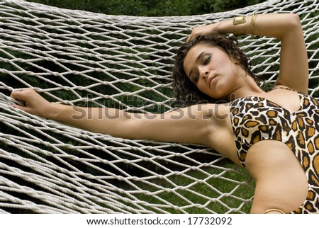 Sexy brunette stretched out in a white hammock on a sunny day - stock photo