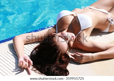 Sexy brunette tans by the pool - stock photo