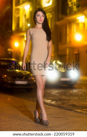Sexy brunette wearing beige dress posing on the pavement - stock photo