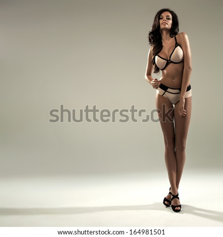 Sexy brunette wearing lingerie on grey background  - stock photo