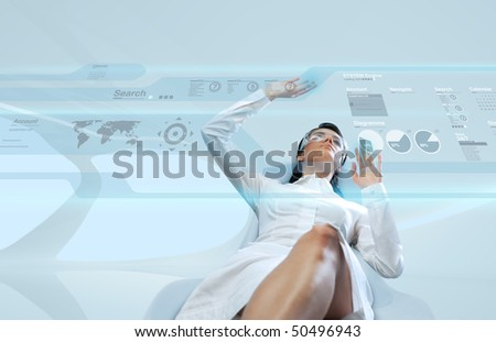 Sexy brunette wearing white suit logging into the system (Attractive young adults in futuristic interfaces / interiors series) - stock photo