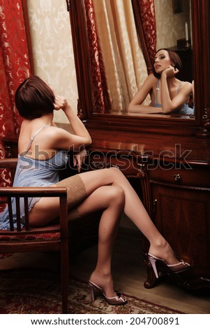 sexy brunette with long legs posing next to the mirror - stock photo
