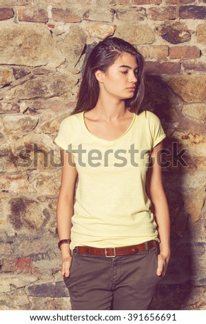 Sexy brunette with modern clothes standing outside and posing against stone wall - stock photo