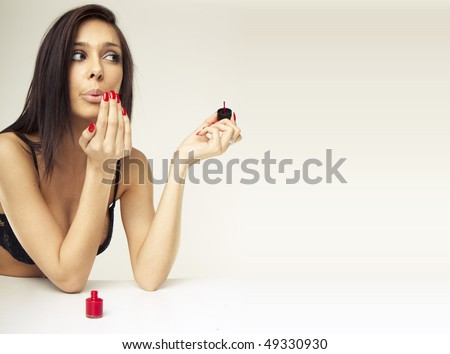 sexy brunette woman doing her nails - stock photo
