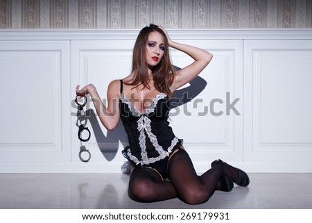 Sexy brunette woman holding handcuffs at vintage wall - stock photo